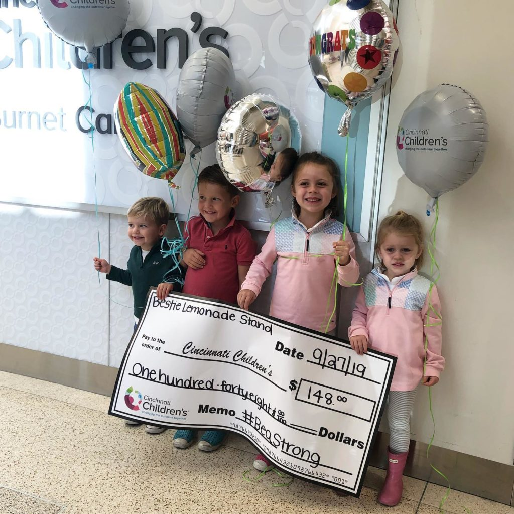 four little kids holding giant check for $148
