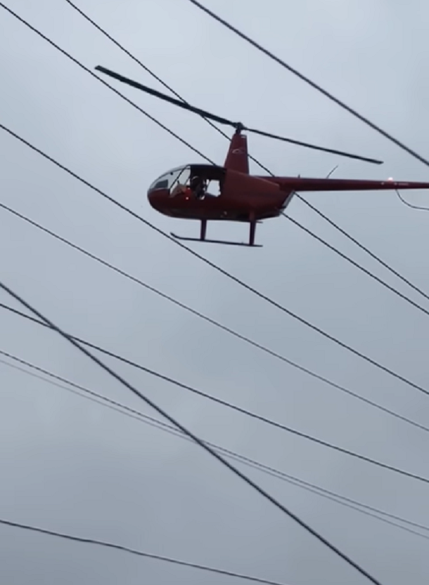 red helicopter flying near power lines with clouds behind