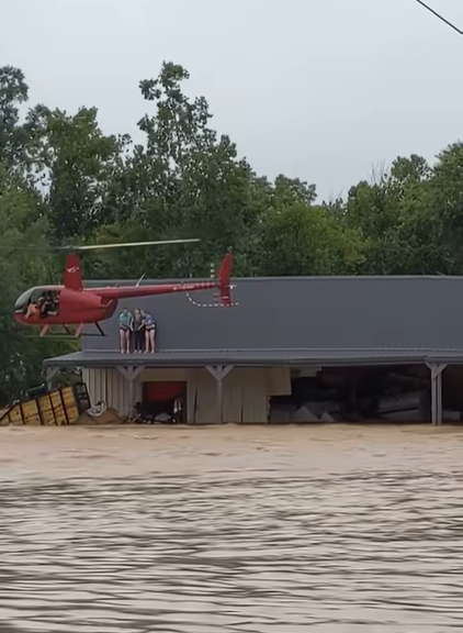 red helicopter hovering by three women on roof of flooded home