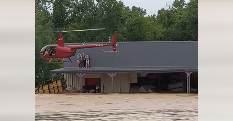 helicopter rescuing three people from roof of flooded home