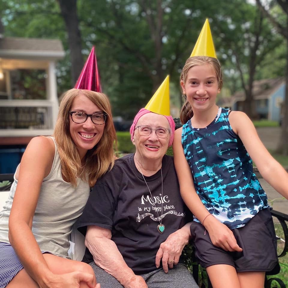 mom and daughter smiling with 93-year-old in party hats