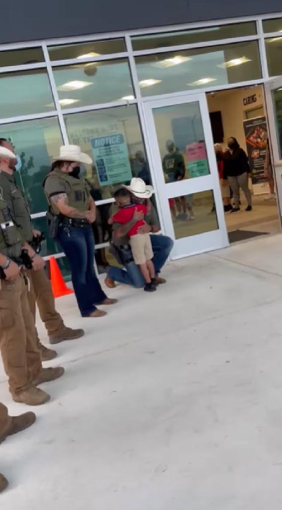 deputy hugging little boy outside school