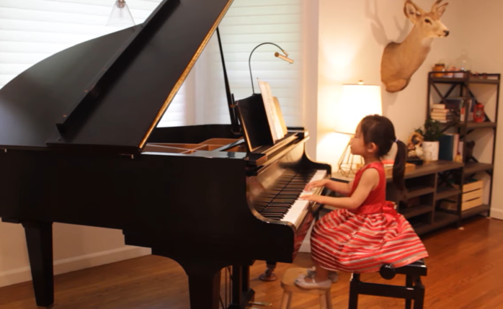 4-year-old playing piano in red dress with feet on tiny stool