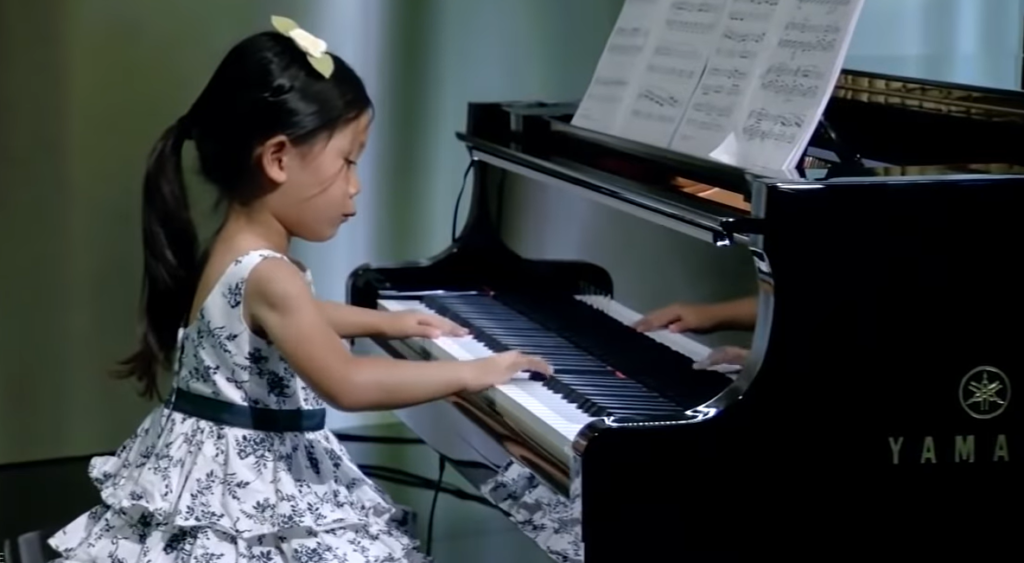 4-year-old playing piano in white and black floral dress