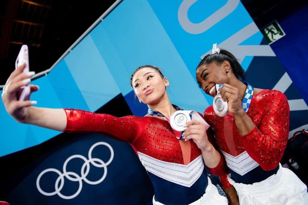 suni lee and simone biles holding medals at the olympics