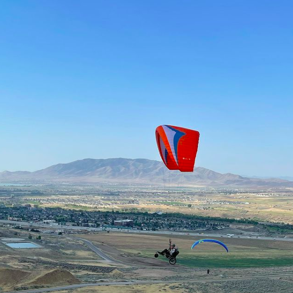 person paragliding in adaptive wheelchair