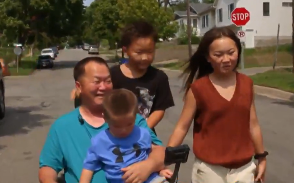 dad in wheelchair holding son on lap with other family members beside him on road