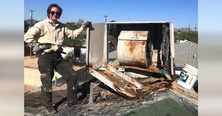 woman standing on roof by super rusty AC unit