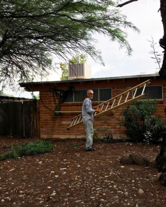 man holding ladder outside home