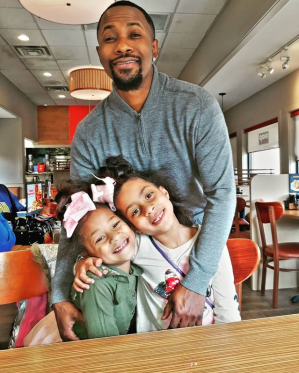 man smiling and standing with his arms around two little girls who are sitting at a restaurant table and smiling