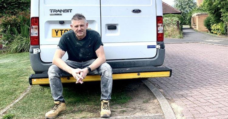 man sitting on back bumper of car
