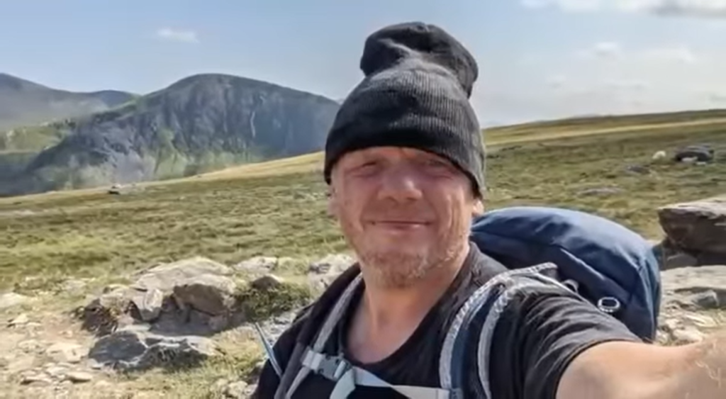 man wearing a hat and backpack near a mountain and taking a selfie