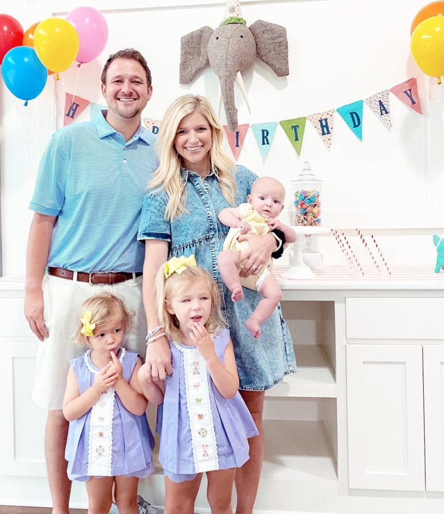 parents with two daughters and infant son in front of happy birthday sign