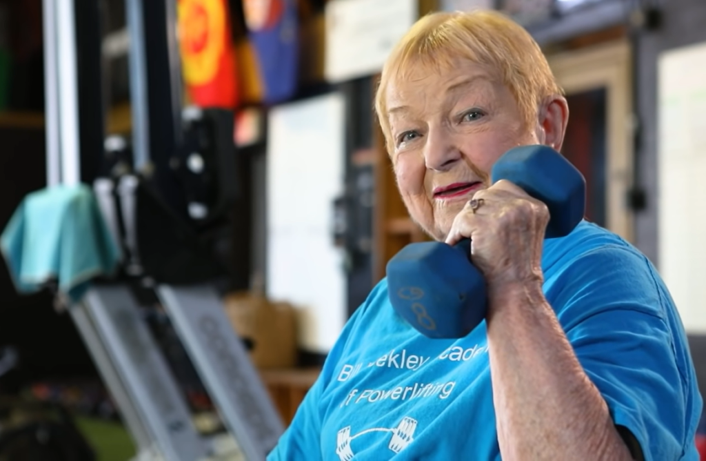 100-year-old woman holding blue dumbbell