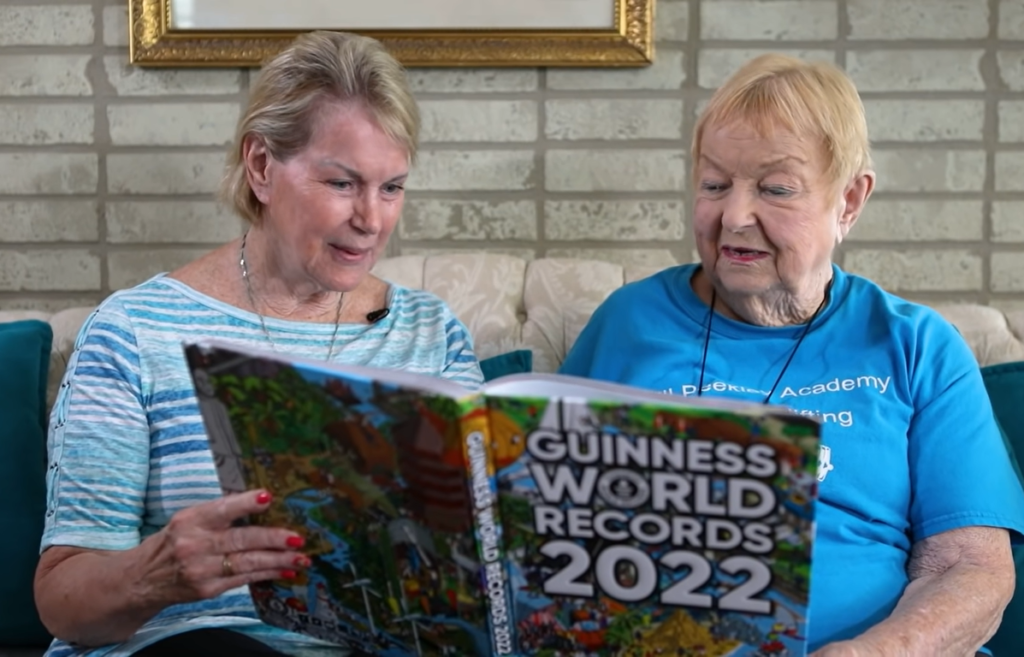 """women looking at """"Guinness World Records 2022"""" book"""