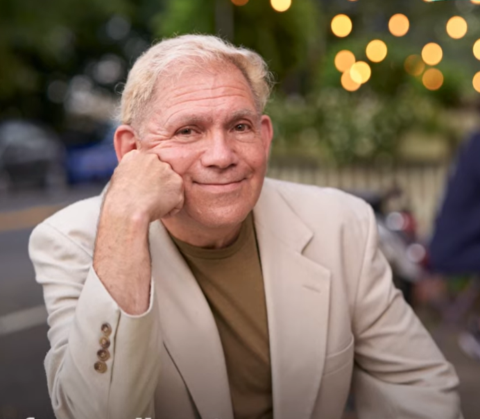 older man smiling at camera with chin on one hand
