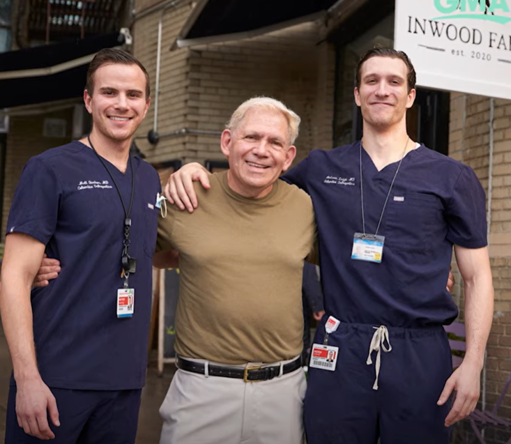 jazz singer in brown shirt smiling with two doctors in scrubs