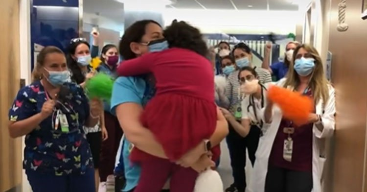 little girl hugging nurse with other nurses cheering behind them