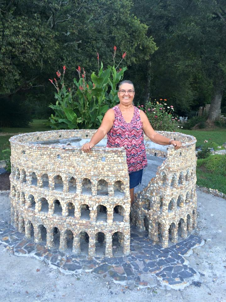 woman standing in middle of pebble Colosseum