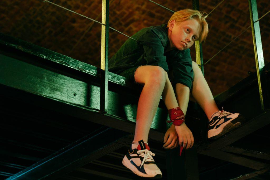 young boy sitting on edge of platform