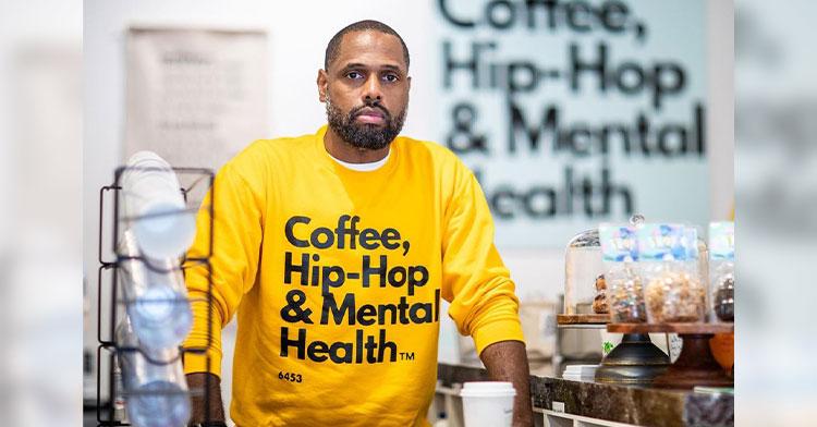 man standing in mental health focused coffee shop