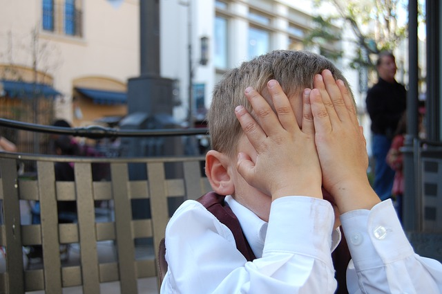 little boy with hands over his face