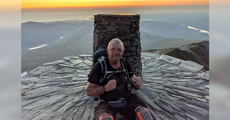 double amputee sitting on mountain peak at sunset