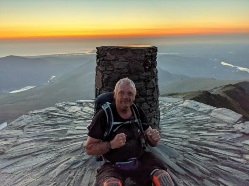 man smiling on top of mountain peak at sunset