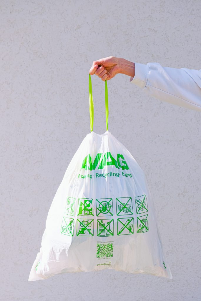 someone holding up recycling bag against blank wall