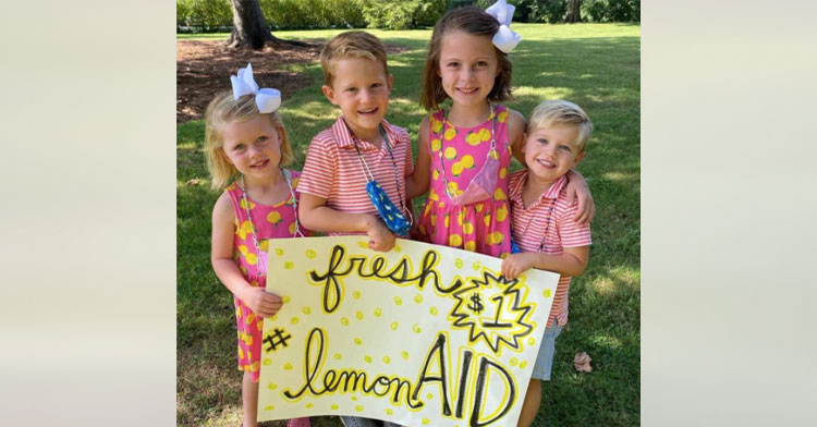 """four kids holding sign that reads """"lemon-aid"""""""