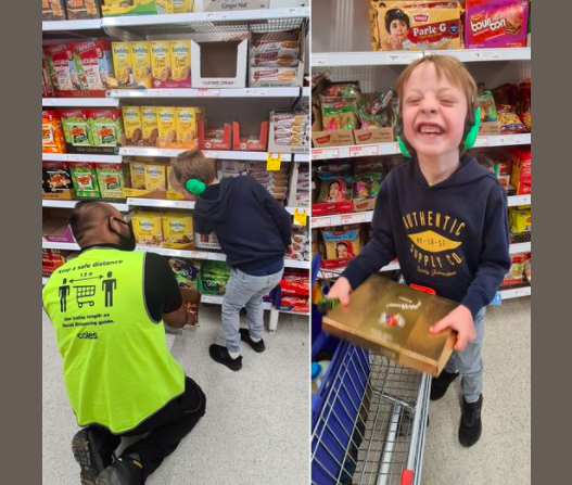 supermarket employee showing little boy cookies next to little boy holding box of chocolates