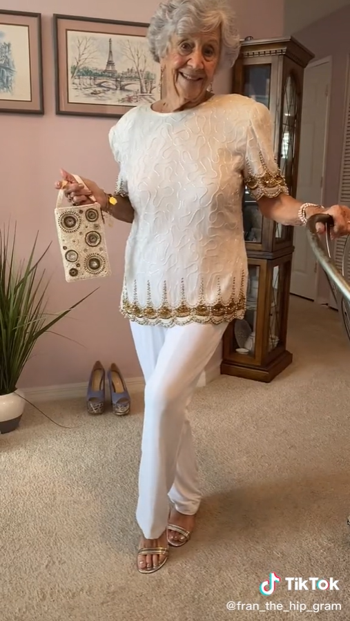old woman smiling and dressed in a fancy white outfit