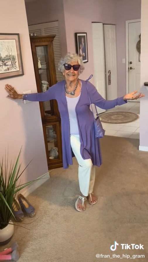 old woman smiling while leaning against a wall inside a home while she wears sunglasses