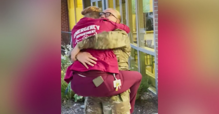 woman in military uniform hugging and holding a healthcare worker who has her legs wrapped around her