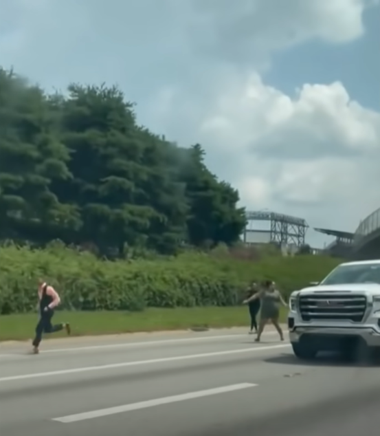 people running beside a truck trying to get the driver's attention