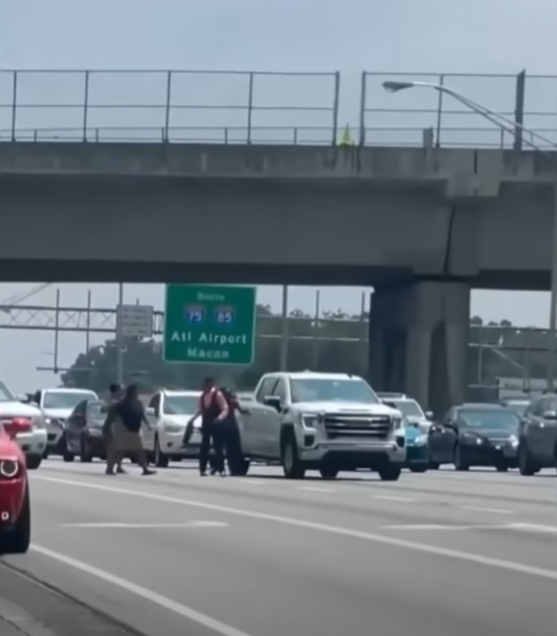 group of people standing near a white truck on a busy highway