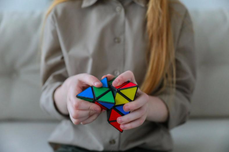 girl holding bright brainteaser in hands