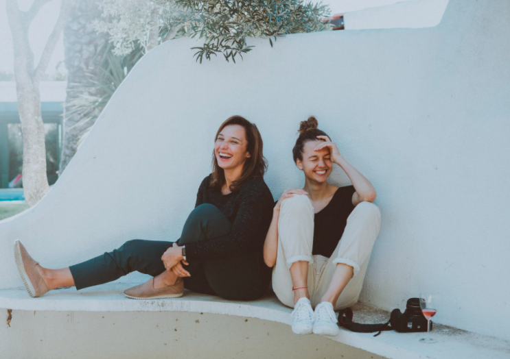 two women laughing on white bench