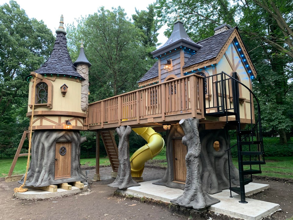 rapunzel inspired children's wooden tower and cottage in a backyard