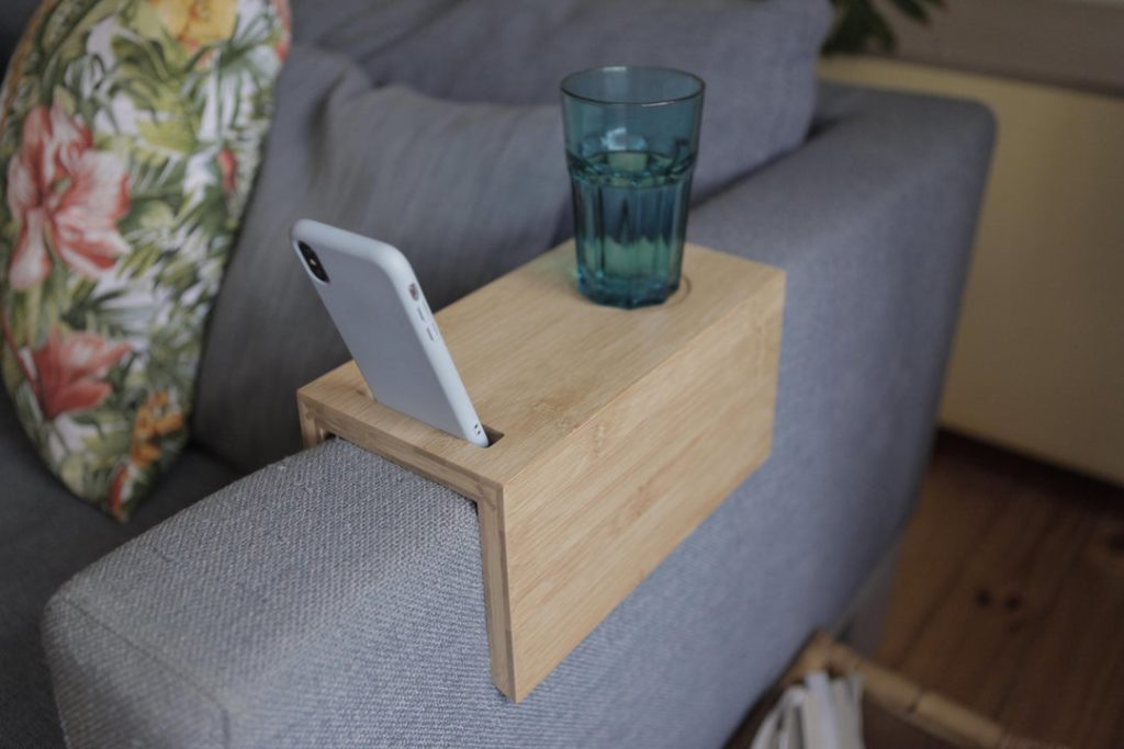 couch with a wooden sofa arm trey that is holding a cup and cell phone