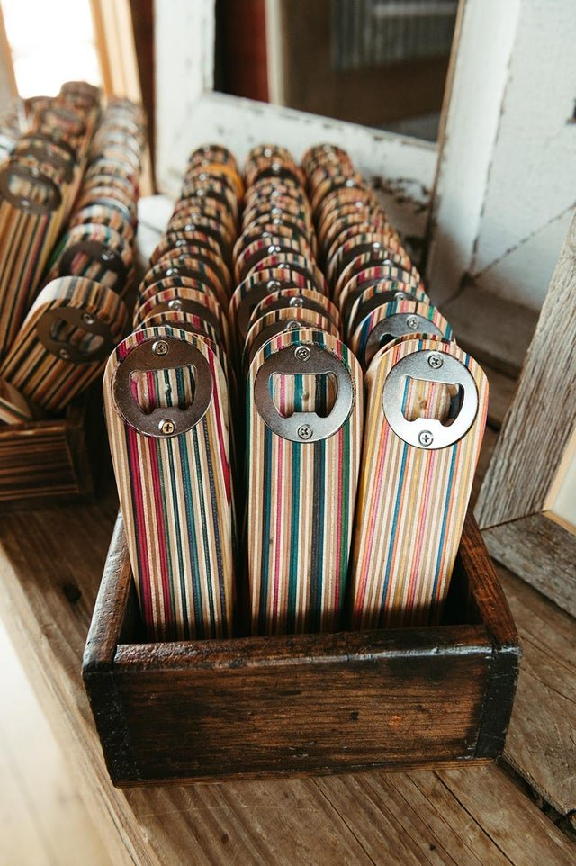 wooden bottle openers made from skateboards lined up in rows