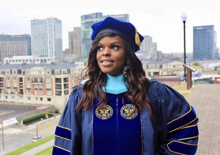 woman wearing graduation clothes and staring into the distance with the city behind her