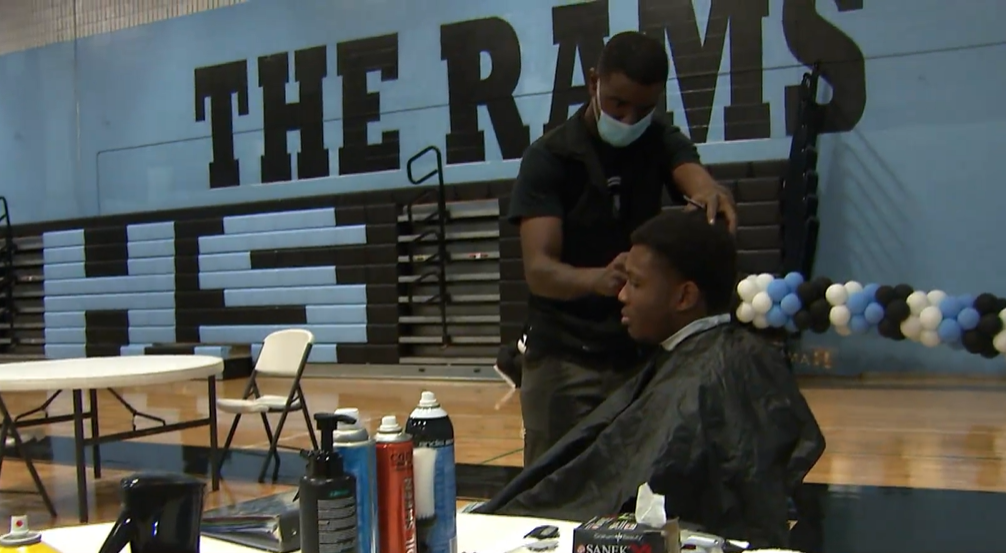 man cutting a teenage boy's hair in a school gym