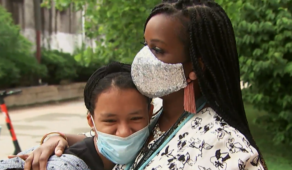 woman wearing a sparkly mask and hugging a high school student who is also wearing a mask