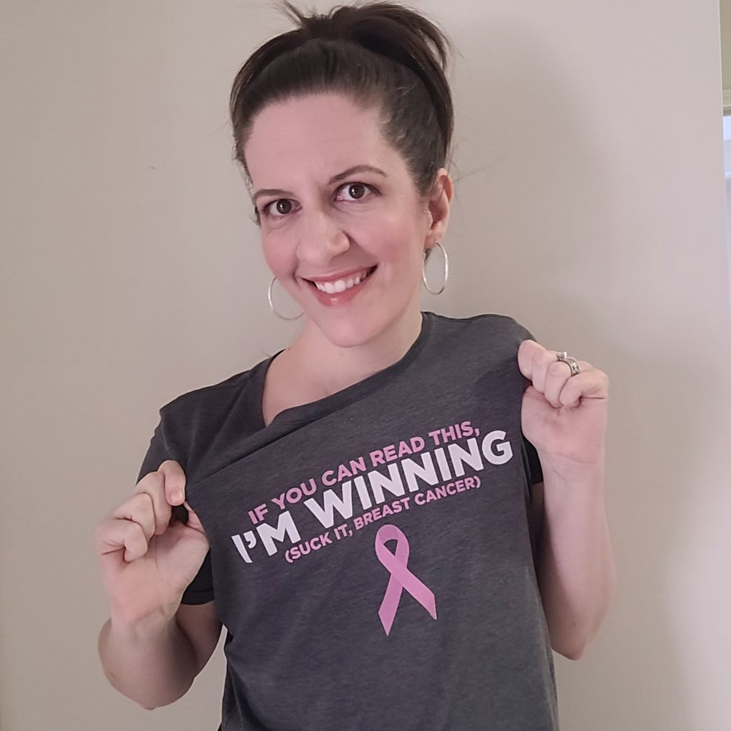 """woman wearing shirt that reads """"if you can read this, i'm winning (suck it, breast cancer)"""""""