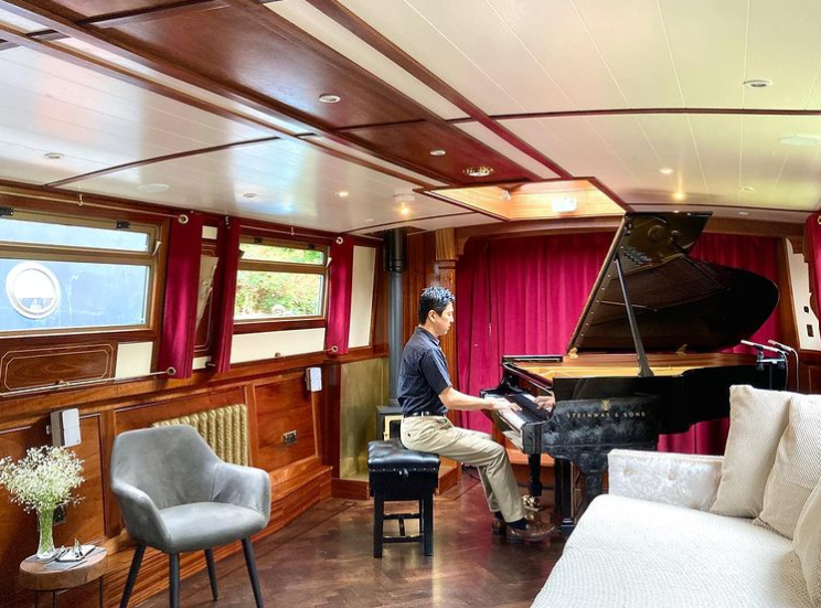 man playing a grand piano on a small canal boat