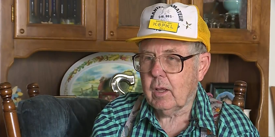 old man sitting in his home wearing glasses and a hat