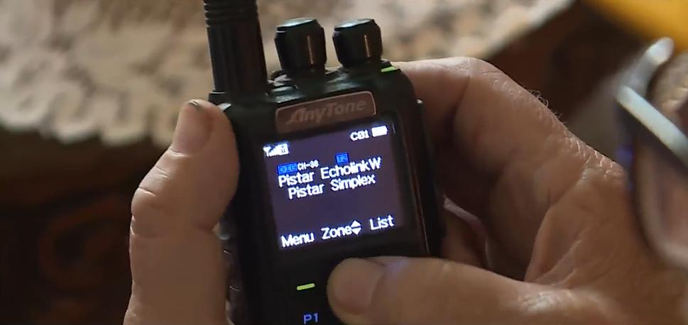 hands holding a small black ham radio