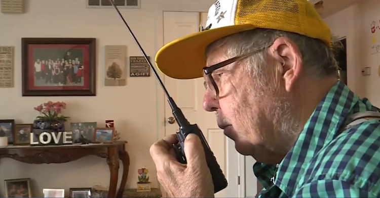 old man using a small black ham radio to talk