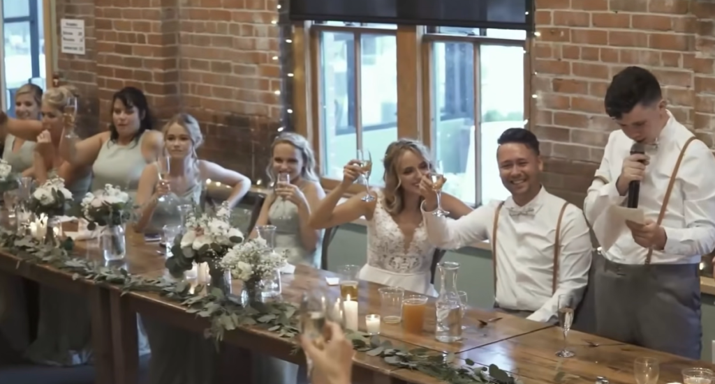 bride and groom with wedding party raising their glasses to toast while one man stands and talks with a microphone